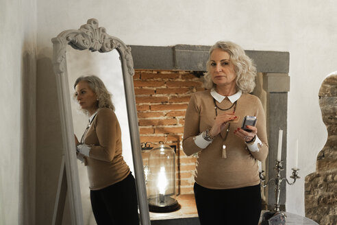 Portrait and mirror image of mature businesswoman with beauty mirror - FBAF00416