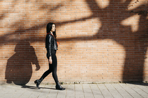 Young woman with a red bag walking in front of a brick wall and a shadow of tree - JRFF03082