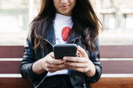 Young woman sitting on a bench, using smartphone - JRFF03088