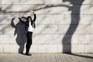 Young woman making shadows on a white wall with a shadow of a tree - JRFF03091