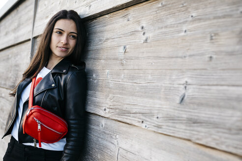 Happy young woman with a red hip bag leaning on wooden wall - JRFF03139