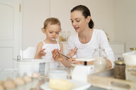 Mother and little daughter making a cake together in kitchen at home - DIGF06770