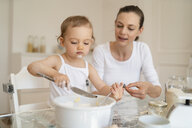 Mother and little daughter making a cake together in kitchen at home - DIGF06773