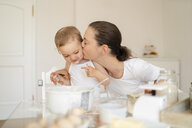 Mother kissing little daughter while making a cake together in kitchen at home - DIGF06776