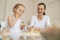 Mother and little daughter making a cake together in kitchen at home - DIGF06779