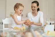 Mother and little daughter making a cake together in kitchen at home - DIGF06782