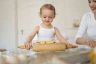 Mother and little daughter with dough roll making a cake together in kitchen at home - DIGF06785