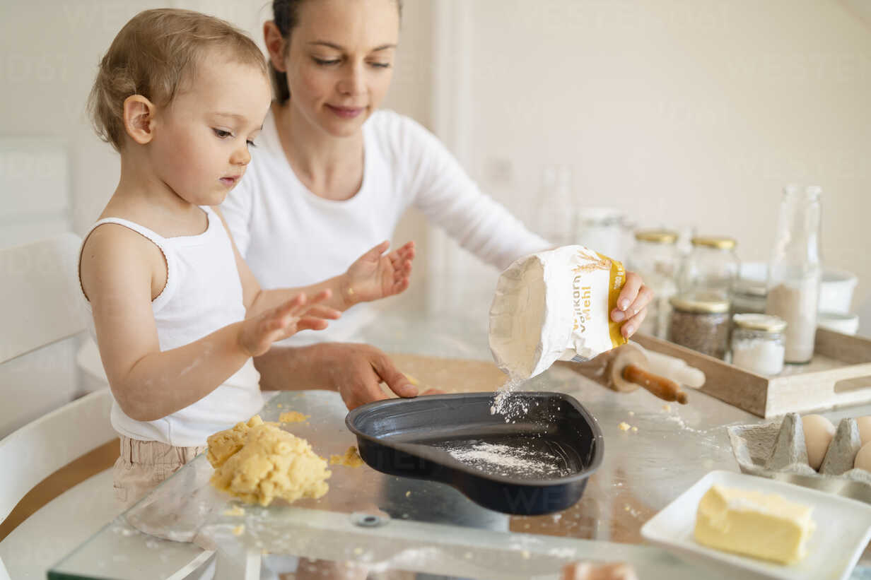 Mother and little daughter making a cake together in kitchen at home - DIGF06788 - Daniel Ingold/Westend61