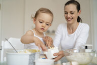 Mother and little daughter making a cake together in kitchen at home - DIGF06791