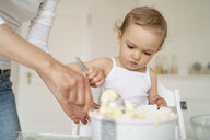 Mother and little daughter making a cake together in kitchen at home - DIGF06794