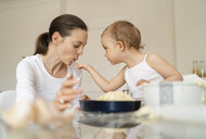 Little girl feeding mother while making a cake in kitchen at home - DIGF06797
