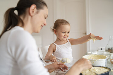 Mother and little daughter making a cake together in kitchen at home - DIGF06800