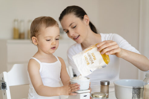 Mother and little daughter making a cake together in kitchen at home weighing flour - DIGF06803