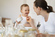 Mother tickling little daughter while making a cake together in kitchen at home - DIGF06806