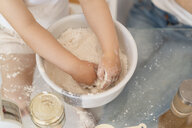 Close-up of girl making a cake mixing flour in a bowl - DIGF06809