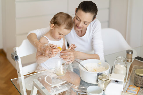 Mother and little daughter making a cake together in kitchen at home - DIGF06815