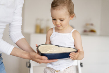 Little girl and mother holding a baking pan with cake batter together in kitchen at home - DIGF06818