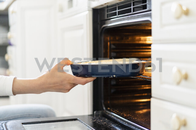 Close-up of woman putting cake batter into the oven - DIGF06821 - Daniel Ingold/Westend61