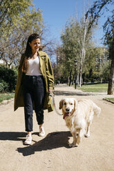 Happy woman going walkies in city park with her Labrador Retriever - JRFF03142