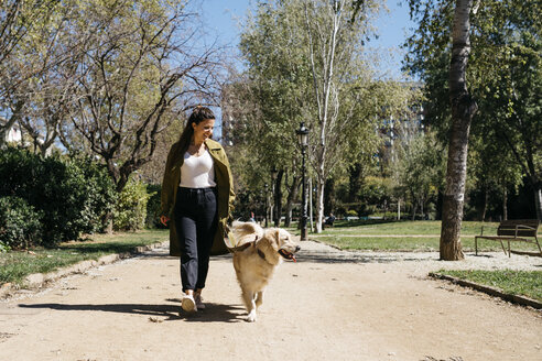 Happy woman going walkies in city park with her Labrador Retriever - JRFF03145