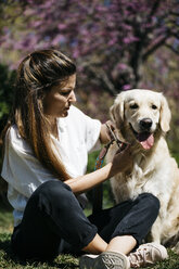 Woman and Labrador Retriever  sitting on meadow in city park - JRFF03151