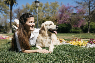 Happy woman lying on meadow in city park with her Labrador Retriever enjoying sunlight - JRFF03154