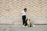 Woman standing in front of patterned brick wall talking to her Labrador Retriever - JRFF03157