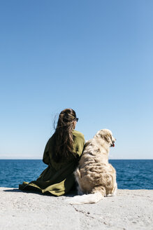Back view of woman sitting besides her Labrador Retriever at quay looking to the sea - JRFF03163