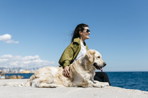 Happy woman sitting besides her Labrador Retriever at quay looking to the sea - JRFF03166
