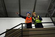 Workers instructing colleague in factory - ZEDF02231