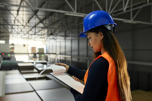 Female worker checking documents in factory warehouse - ZEDF02240