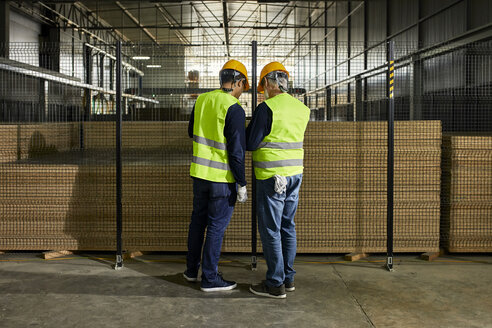 Rear view of workers standing at grid in factory - ZEDF02243
