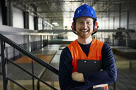 Portrait of happy worker in factory warehouse - ZEDF02246