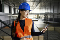 Smiling female worker using tablet in factory warehouse - ZEDF02249