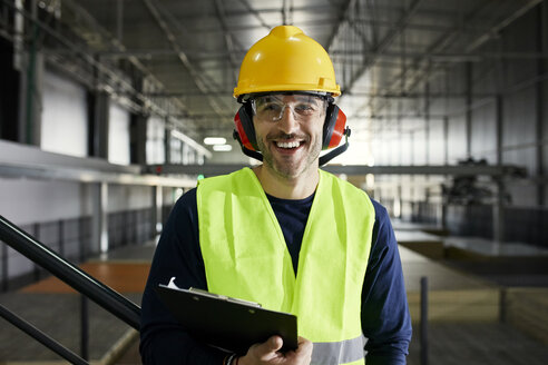 Portrait of happy worker in factory warehouse - ZEDF02252