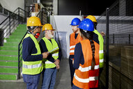 Workers standing in factory warehouse talking - ZEDF02255