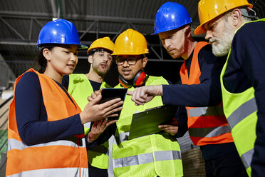 Workers in factory warehouse talking and using tablet - ZEDF02258