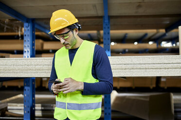 Worker using cell phone in factory warehouse - ZEDF02264