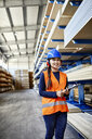 Smiling female worker with ear muffs and clipboard in factory warehouse - ZEDF02267