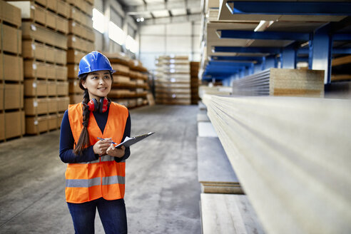 Smiling female worker with clipboard in factory warehouse - ZEDF02270
