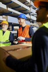 Happy workers talking in factory warehouse - ZEDF02276