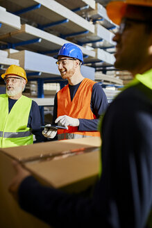 Happy workers talking in factory warehouse - ZEDF02276
