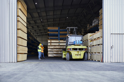 Two workers standing in factory warehouse next to forklift - ZEDF02279