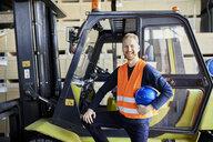 Portrait of happy worker at forklift in factory - ZEDF02282