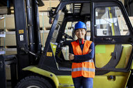 Portrait of confident female worker at forklift in factory - ZEDF02285
