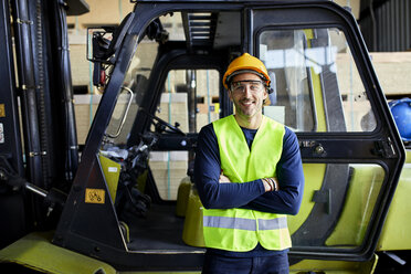 Portrait of confident worker at forklift in factory - ZEDF02288