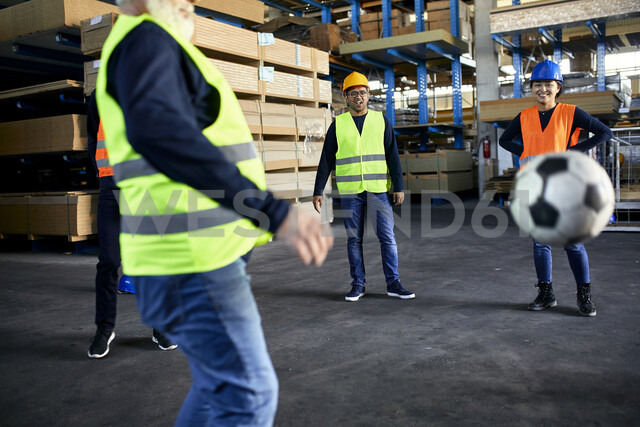 Workers playing football in factory warehouse - ZEDF02291 - Zeljko Dangubic/Westend61