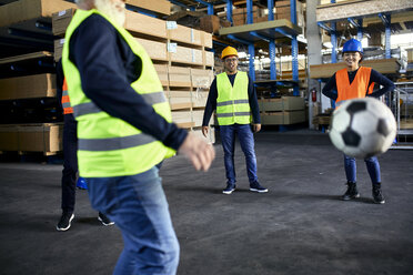 Workers playing football in factory warehouse - ZEDF02291