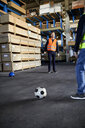 Workers playing football in factory warehouse - ZEDF02294