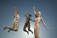 Multi-ethnic women in bathing suits jumping - BLEF00015